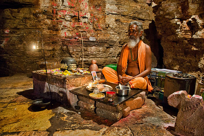 The priest inside the Agastya cave temple at Yaganti - behind the Shiva Linga that the famed Sage installed and worshipped on.