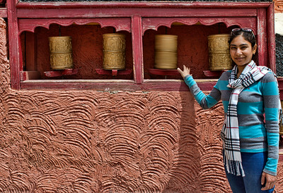 Smitha squints in the harsh light, while turning the prayer wheels clockwise for good luck