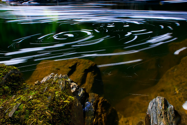 The foam from the waterfall floats on the surface of the water, and a long exposure shows how the waterflow spirals atop the surface